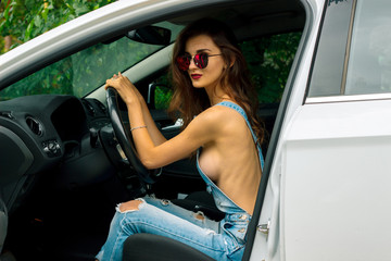 young Sexy brunette with naked body in jeans jumpsuit sits in the car