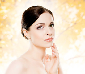 Portrait of young, beautiful and healthy woman: over orange background. Healthcare, spa, makeup and face lifting concept.