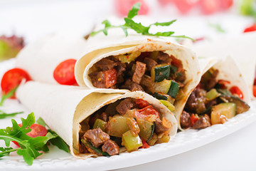 Burritos wraps with beef and vegetables on a light  background.