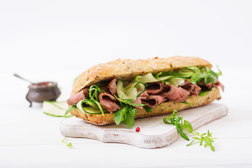 Sandwich of whole wheat bread with roast beef, cucumber and arugula.