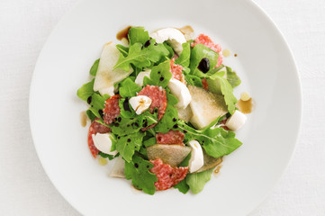 salad with melon, arugula, salami, and mozzarella sprinkled with olive oil and balsamic vinegar