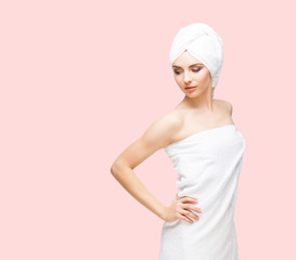 Young, beautiful and natural woman wrapped in towel over orange background.