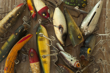 Wet antique fishing lures viewed from above on a rough wood surface