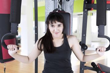Beautiful woman sitting on the gym equipment