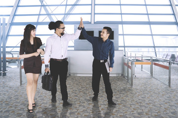 Business people giving high five at the airport
