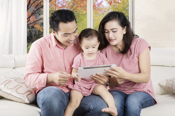 Cheerful family with digital tablet on couch