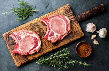 Raw pork cutlet chop for fry on pan with herbs, garlic on wooden boards, slate gray background