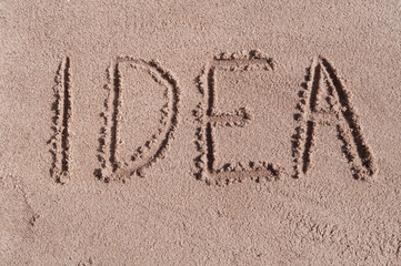 "Handwritten word ""IDEA"" on brown sand on the beach in sunny day"