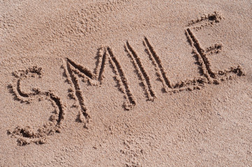"Handwritten word ""SMILE"" on brown sand on the beach in sunny day"