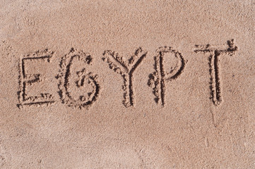 "Handwritten word ""EGYPT"" on brown sand on the beach in sunny day"