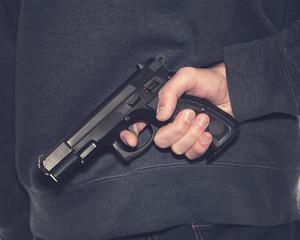 Shooter with handgun wearing dark blue jeans and hoodie over dark background