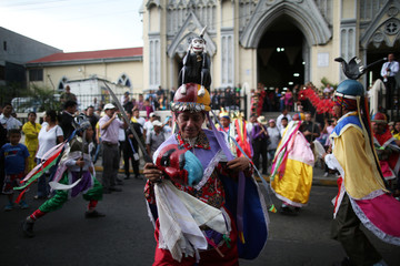 Traditional dancers participate in a procession to commemorate the Feast of the Savior of the World in San Salvador