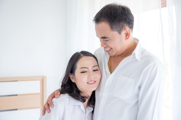 Asian couple smiling together after waking up in the morning
