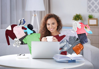 Beautiful young woman with cup in hands using laptop