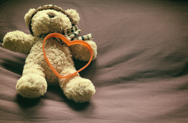Teddy bear with red heart shape on bed. Valentine concept.
