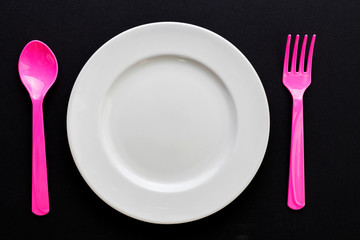 Empty plate with spoon and fork on black background
