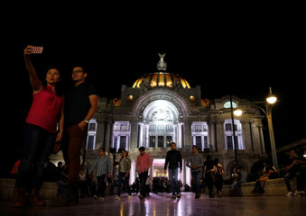 A couple takes a selfie outside at the Bellas Artes Palace in Mexico City