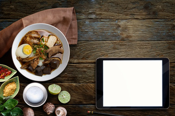 Paste of rice flour with pork, Blank screen tablet and Chinese roll noodle soup over wooden table.