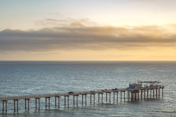 The Scripps pier and sunset on the horizon in California
