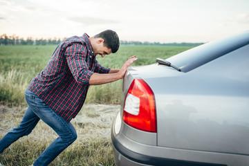 Man pushing broken car, side view