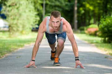 runner man in start position in a park in summer