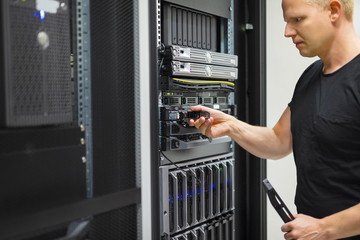 IT Engineer Installing Hard Drive In Rack Server