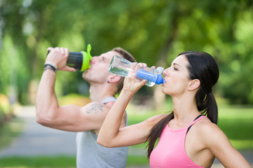 man and woman drinking water in a park in summer