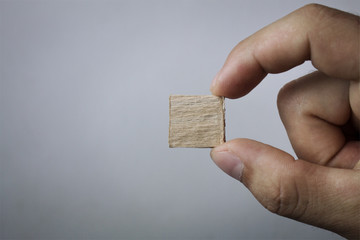 Hand holding small wood cube.