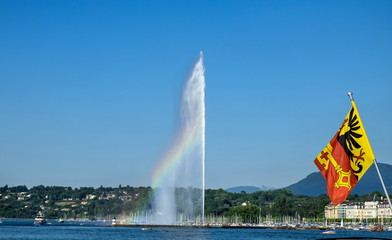 The rainbow on Jet d'Eau -  large fountain in Geneva and flag of the medieval bishopric of Geneva. Switzerland