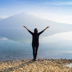 The joy of unity with nature. A woman is standing by the lake. Hands are open and raised above the head. Majestic mountain landscape. Switzerland.