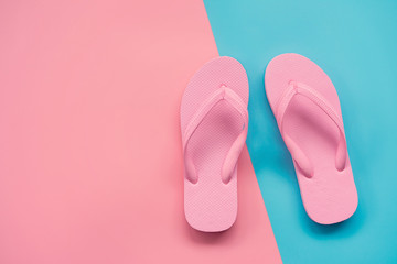 pink sandals on pink and blue pastel background. Summer concept with copy space.