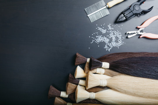 Set of sevral color hair extension tools on a dark background