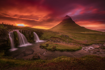 Colorful midnight sunset at Kirjufell in summer with a view mountain, waterfall and cloudy sky of
