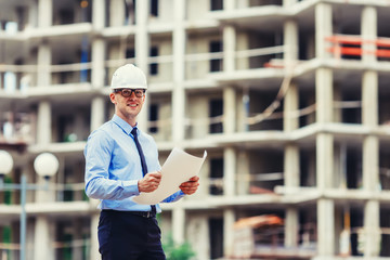 Handsom construction engineer at the construction site looking at the camera