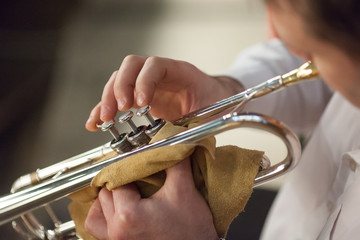 perfomance, talent, passion concept. close up of great brass instrument, shiny trumpet, in aristocratic hands of professional jazzman wearing in formal white shirt