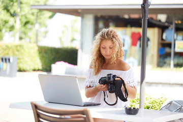 woman outdoors using a digital reflex to take pictures and check on her laptop what she made