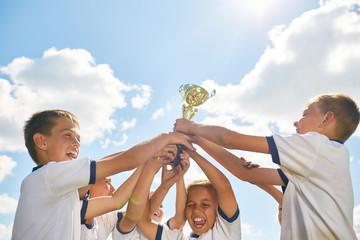 Boys Sports Team Holding Trophy