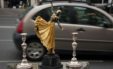 Oriental dancer figurine at flea market and blurry cars traffic at background. Paris, France