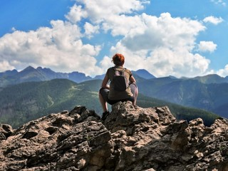 A girl rests on top of a mountain admiring the mountains in the clouds