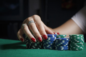 The girl at the poker table is holding chips