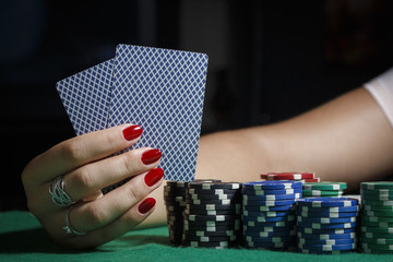 The girl at the poker table is holding cards