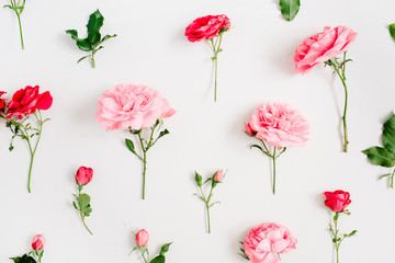 Floral pattern made of pink and red roses, green leaves, branches on white background. Flat lay, top view. Valentine's background. Floral background. Pattern of flowers.