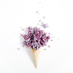 Wall Murals Lilac Waffle cone with lilac flower bouquet on white background. Flat lay, top view floral background.