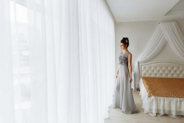 Woman in chic dress, luxury bedroom interior
