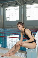 Young woman feeling pain in her foot at swimming pool. Sports exercising injury