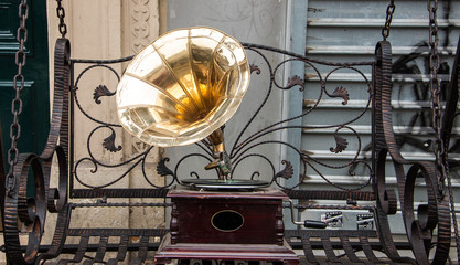 Gramophone standing on the vintage swing at flea market in Paris (France). Old times background.