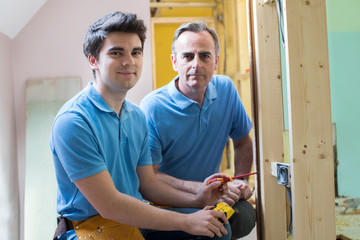 Portrait Of Electrician With Apprentice Working In New Home