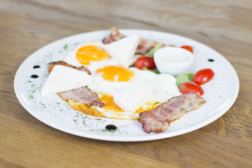 Fried eggs with bacon on the wooden table. Tomato and cheese on the side.