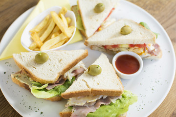 Club sandwich with chicken breast, bacon, tomato, cucumber, and herbs. French fries on the side.