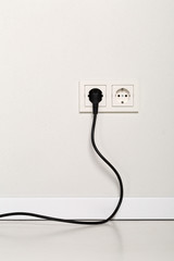 Black power cord cable plugged into european wall outlet on white plaster wall